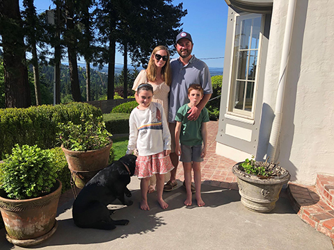 Patrick and his family, w/ dog, standing outside.