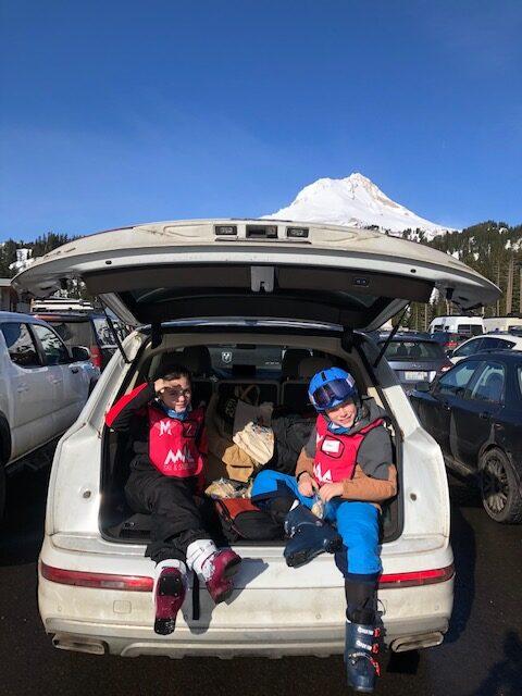 Patrick's family in full ski gear, sitting in the back of a car.