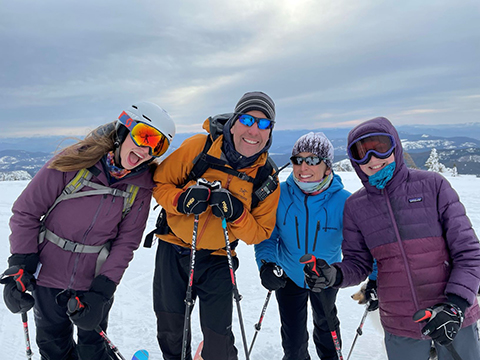 Mike and his family atop a mountain peak in skiing gear